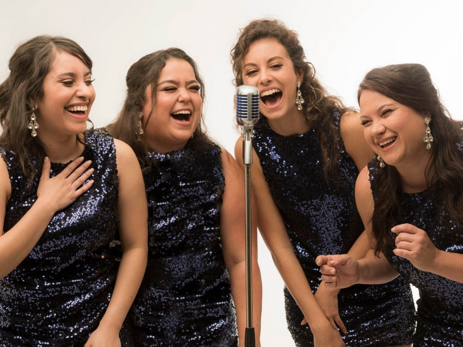 The Sapphires in sequins singing at microphone