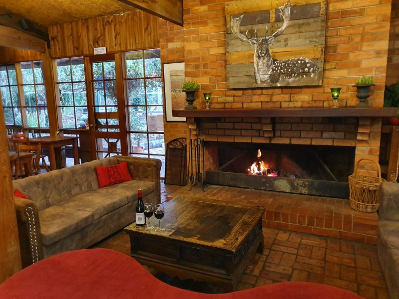 Lit fire in a brick fireplace surrounded by comfy couches and coffee table