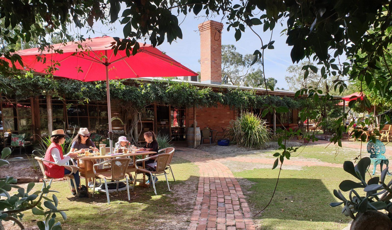 Red umbrella over garden diners