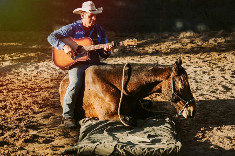 Tom Curtain singing while seated on Legend the Horse at the Katherine Outback Experience
