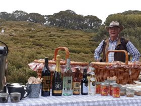 Ken Bell our storyteller, stands beside the picnic spread with a view of the walkers coming to join