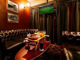 Private booth with leather couches and flat screen