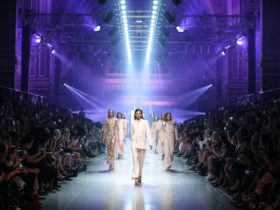 Finale Runway from the 2018 Festival, featuring seven models all dressed in white and gold.