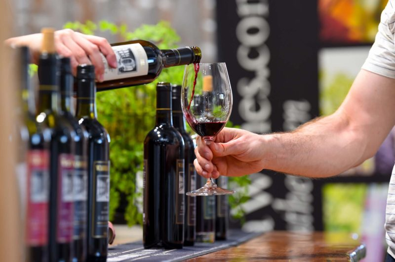 The tasting line up at Warrabilla cellar door is artfully unfocused with a glass being poured.