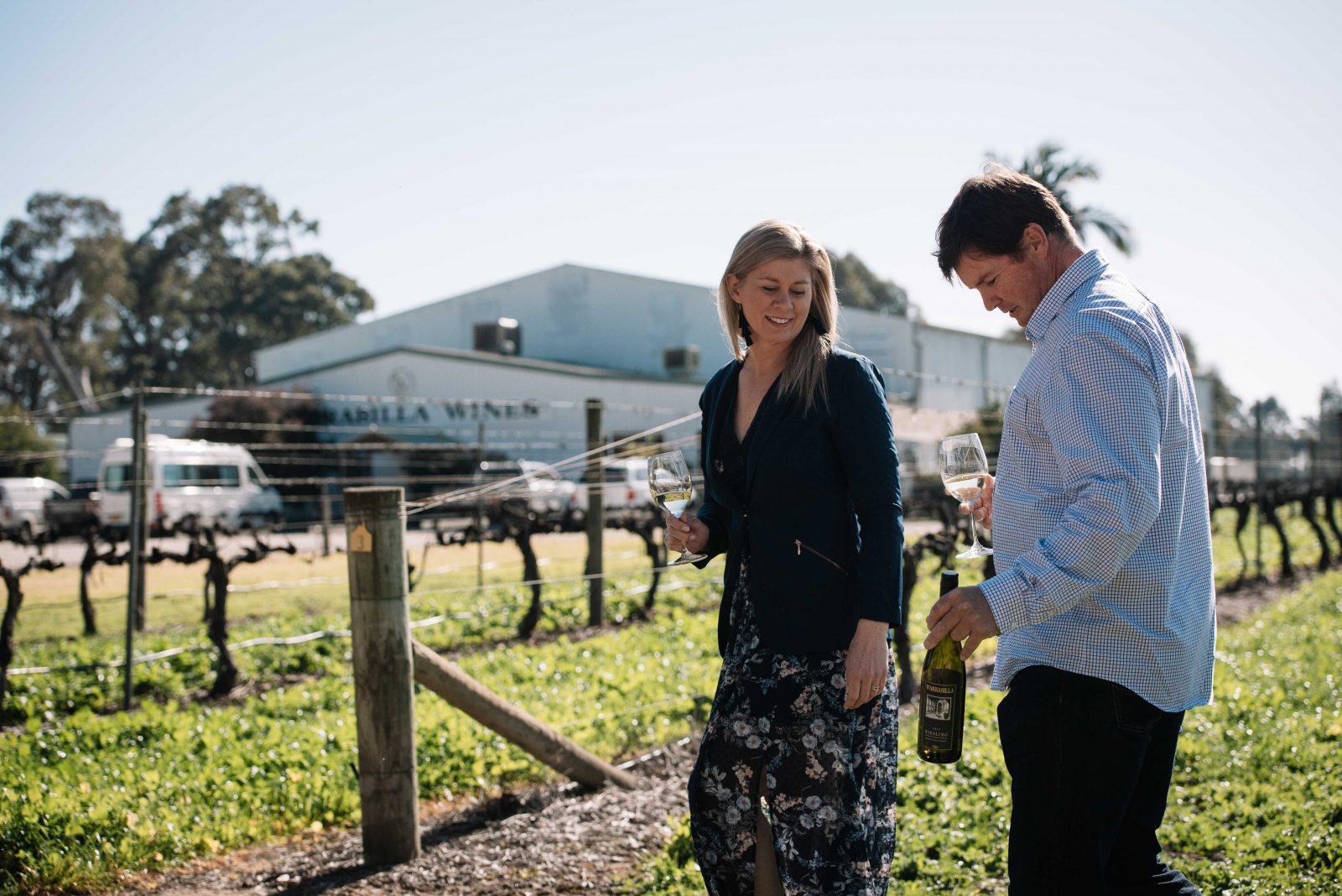 A handsome couple stands in a vineyard infront of the Warrabilla Cellar door.